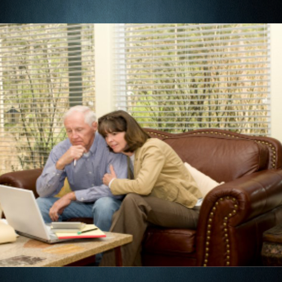 A middle-aged couple sitting on their leather sofa are examining their finances on their laptop