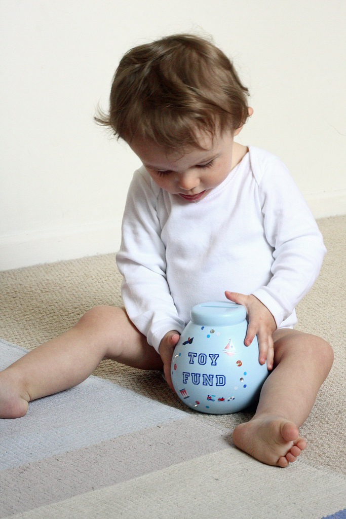 A young child learning to save as she examines a piggy bank.